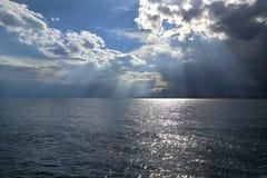 云彩和太阳光芒在海 免版税库存图片