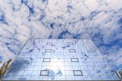 云彩和太阳在杯被反射一个现代大厦的窗口 底视图 库存照片
