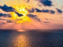 云彩和太阳设置在海湾 免版税库存照片