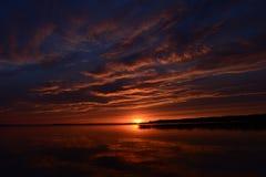 云彩和日落在水反射了在黄昏 库存图片