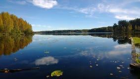 云彩和森林的反射在镇静湖在秋天 库存照片