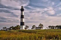 云彩和沼泽地围拢的灯塔 免版税库存照片