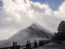 云彩和薄雾在路旁山 免版税库存图片