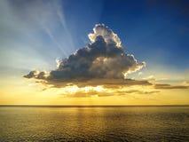 云彩在金黄海的Raylight日落 库存图片