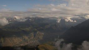 云彩时间间隔在位于山峡谷的村庄的 股票视频