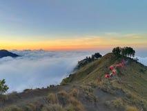 云彩海在山上面和小组的五颜六色的帐篷 免版税库存图片