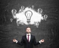 云彩的冥想的人与电灯泡作为新的企业想法的概念 黑粉笔板作为背景 免版税库存照片