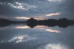 云彩的反射在日落期间的 射击在湖在一个消遣公园 免版税库存照片