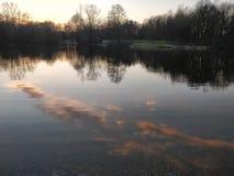云彩的反射在水中在日出或日落 免版税库存照片