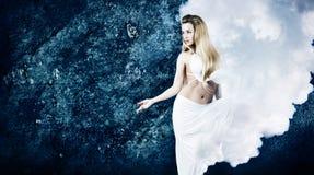 云彩礼服的白肤金发的妇女在难看的东西蓝色墙壁 免版税库存照片