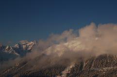 云彩围拢的山峰顶 库存图片