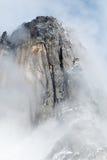 云彩围拢的花岗岩尖顶 图库摄影