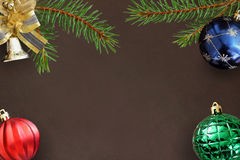 云杉、蓝色、绿色有肋骨,红色波浪气球和装饰响铃圣诞节分支在黑暗 免版税图库摄影