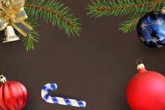 云杉圣诞节分支、棍子、蓝色和红色波浪气球和装饰响铃在黑暗的背景 免版税图库摄影