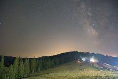 云杉的森林和被点燃的房子在晚上,可看见的银河星系,清楚的天空,长的曝光 免版税库存照片