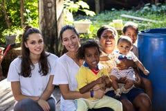 互动与一个亚洲家庭的两个年轻欧洲女孩 免版税图库摄影