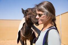 互动与一头逗人喜爱的黑骆驼的微笑的妇女 免版税库存图片