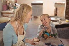 互动与女孩的女性陶瓷工在瓦器车间 库存图片
