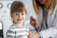 互动与女性医生的微笑的逗人喜爱的矮小的患者 库存图片