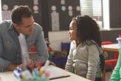 互动与学校女孩的老师的正面图,当坐在教室时 免版税库存图片