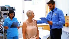 互动与患者的男性医生,当看X-射线时的护士 影视素材