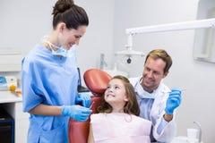 互动与年轻患者的微笑的牙医 免版税库存图片