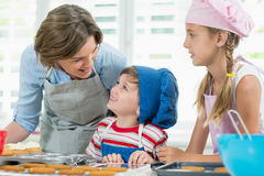 互动互相的微笑的母亲和孩子,当准备曲奇饼时 免版税库存照片