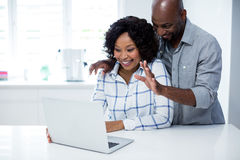 互动互相的愉快的夫妇,当使用膝上型计算机时 免版税图库摄影