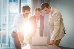 互动使用膝上型计算机的商人和女实业家 免版税库存照片