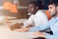 互动在会议上的两个年轻商人的图象在办公室 库存照片