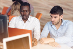 互动在会议上的两个年轻商人的图象在办公室 免版税库存图片
