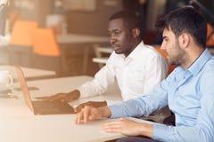 互动在会议上的两个年轻商人的图象在办公室 库存图片