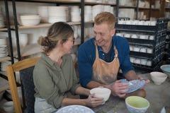 互动男性和女性的陶瓷工,当装饰陶器时 免版税库存照片