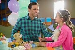 互动的父亲和的女孩,当演奏玩具厨房集合时 免版税库存照片
