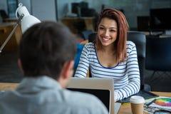 互动的男人和的妇女坐在书桌和 库存照片