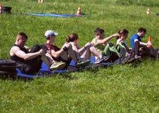 互相执行转移的重量的任务运动员在坐姿 库存照片