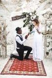 互相看在boho土气样式的婚姻的曲拱附近的新娘和新郎画象  非洲年轻人是 免版税库存照片