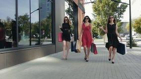 互相谈话三个美妙的女性的朋友步行沿着向下街道和 股票视频