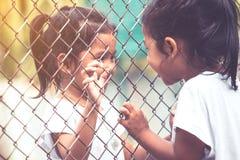 互相谈话两个亚洲拿着钢滤网的孩子和手 免版税库存照片