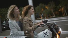 互相谈话两个美丽的少妇骑摩托车在晚上在城市街道和 有他的女朋友的女性骑自行车的人 股票视频