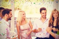 互相谈话的朋友的综合图象,当食用香槟时 免版税库存照片