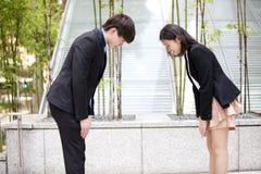 互相鞠躬年轻亚裔的商业主管 免版税库存照片