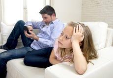 互联网使用手机的上瘾者父亲忽略小哀伤的女儿使孤独和沮丧不耐烦 免版税库存照片