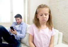 互联网使用手机的上瘾者父亲忽略小哀伤的女儿使孤独和沮丧不耐烦 免版税图库摄影