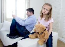互联网使用手机的上瘾者父亲忽略小哀伤的女儿使拥抱玩具熊不耐烦 图库摄影