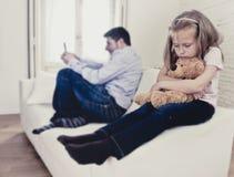 互联网使用手机的上瘾者父亲忽略小哀伤的女儿使拥抱玩具熊不耐烦 免版税库存图片