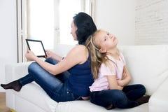 互联网使用数字式片剂垫的上瘾者母亲忽略小哀伤的女儿留给单独乏味 免版税库存照片