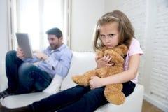 互联网使用数字式片剂垫的上瘾者父亲忽略小哀伤的女儿使拥抱玩具熊不耐烦 免版税库存照片