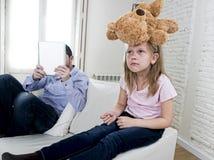 互联网使用数字式片剂垫的上瘾者父亲忽略小哀伤的女儿使拥抱玩具熊不耐烦 图库摄影
