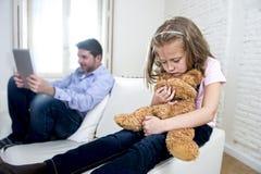 互联网使用数字式片剂垫的上瘾者父亲忽略小哀伤的女儿使拥抱玩具熊不耐烦 库存图片